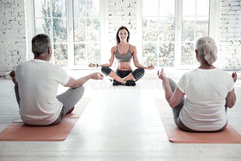 快乐的瑜伽老师与小组退休的人一起使用 免版税库存照片
