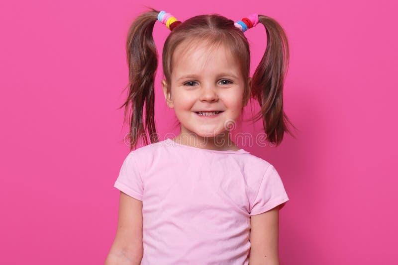 快乐的甜女孩接近的画象有滑稽的猪尾的,恳切地微笑,看直接地照相机,身分 免版税库存照片