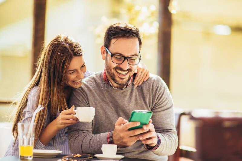 快乐的男女约会,在咖啡馆里,用电话 免版税库存图片