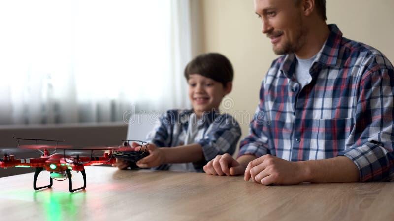 快乐的男孩和他的父亲运行的quadcopter在家,业余时间,设备 免版税库存照片