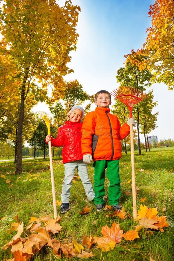 快乐的男孩和女孩有站立在公园的犁耙的 免版税库存图片