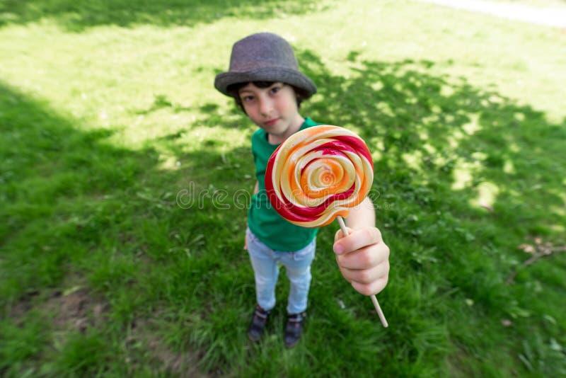 快乐的男孩在他的手上的拿着一个棒棒糖 库存图片