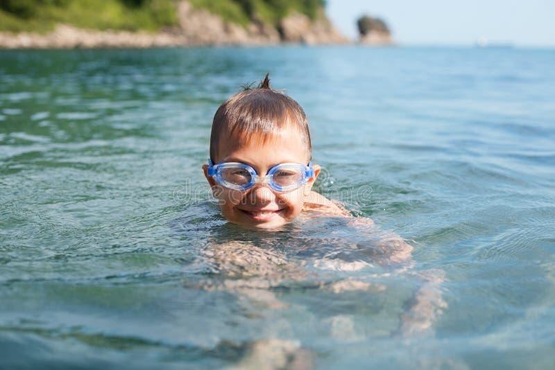 快乐的男孩在海游泳 免版税库存图片