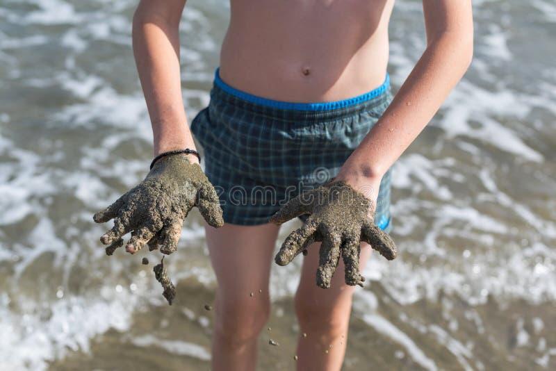 快乐的男孩少年在从海的医治用的医治用的泥显示他的手 免版税图库摄影