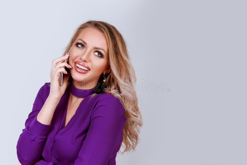 快乐的白肤金发的妇女谈话在智能手机 免版税库存照片