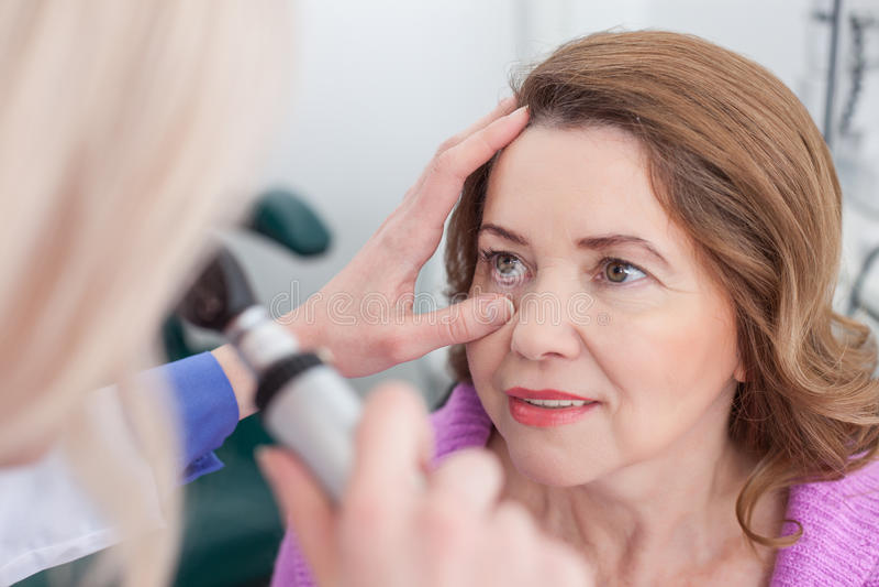 快乐的眼科医生与患者一起使用 库存照片