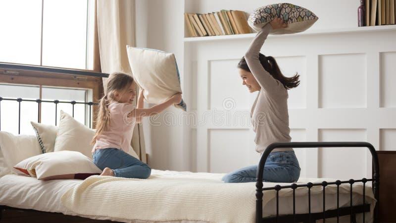 快乐的矮小的拿着枕头的女儿和母亲一起使用 图库摄影