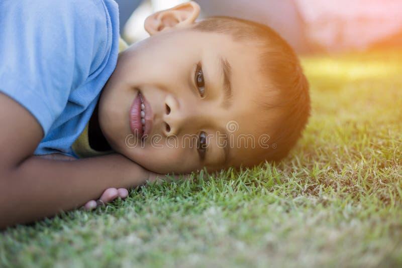 快乐的穆拉托男孩微笑着享受被收养的生活 自然、公园或户外的小男孩肖像 快乐的概念 库存照片