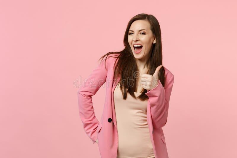 快乐的笑的年轻女人画象看照相机的夹克的,显示赞许隔绝在粉红彩笔墙壁上 免版税库存照片