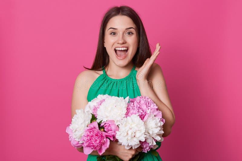 快乐的精力充沛的聪慧的女孩佩带在绿色礼服的,广泛张她的嘴和眼睛,举一只手,看起来愉快 免版税库存照片