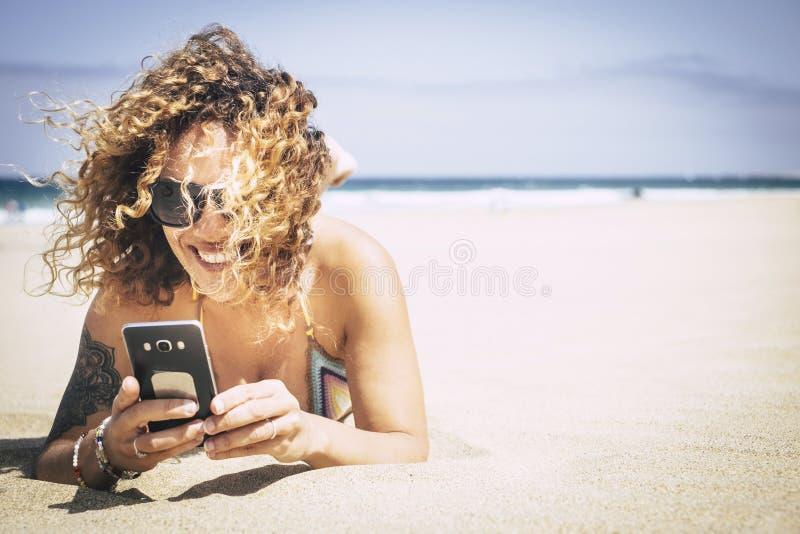 快乐的美好的白种人middlea ge少女微笑和使用手机在海滩连接用朋友和父母 免版税库存图片