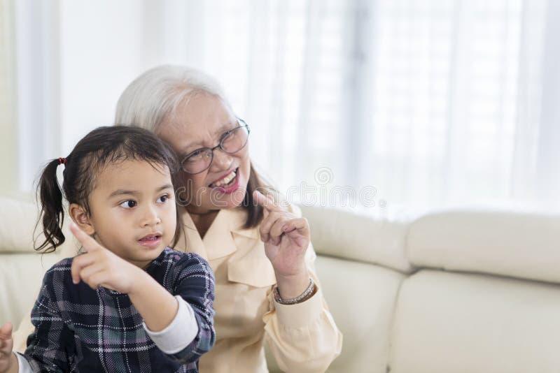 快乐的老妇人看与她的孙的电视 库存照片