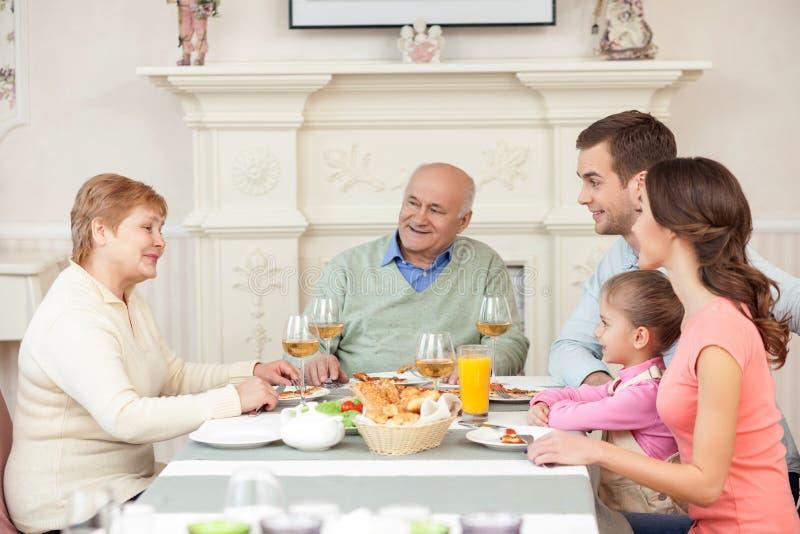 快乐的老已婚夫妇与他们的亲戚用餐 免版税库存图片