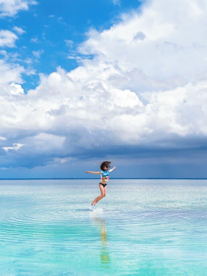 快乐的聪慧的深色的女孩在照片的水跳 一个天堂般的地方,美好的海景,在的云彩 图库摄影