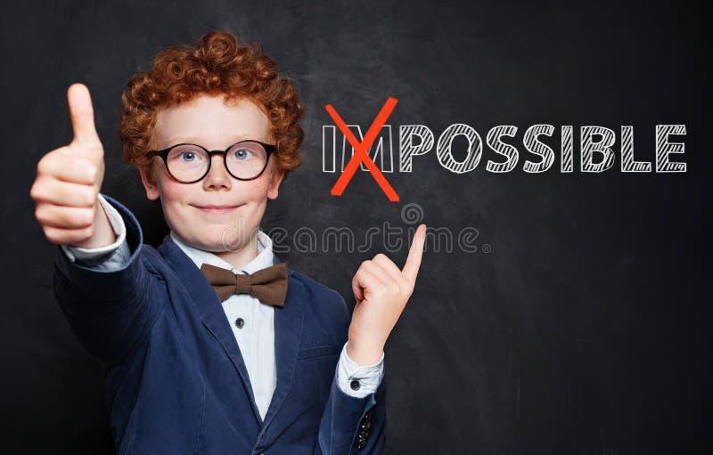 快乐的聪明孩子指着黑板背景上可能的铭文 成功与发展观 库存照片