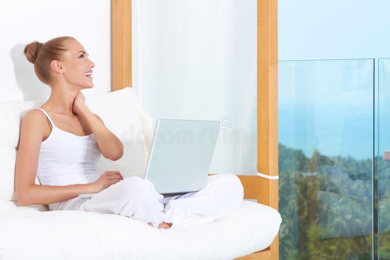 快乐的膝上型计算机笑的妇女 库存照片