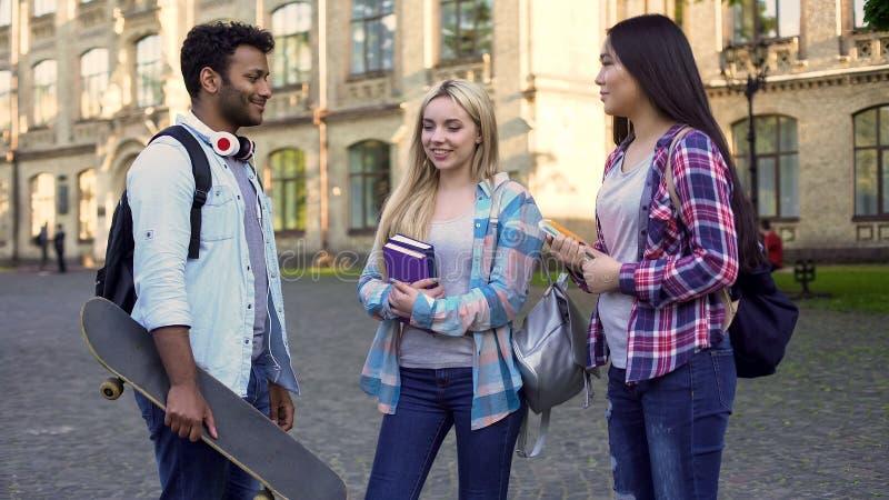 快乐的西班牙男性谈话与女孩在学院,断裂,友谊附近 免版税图库摄影