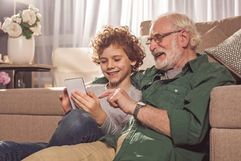 快乐的观看在机动性的爷爷和男孩 库存照片