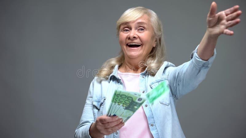 快乐的资深女性投掷的欧元钞票,浪费金钱,出借业务 免版税库存图片