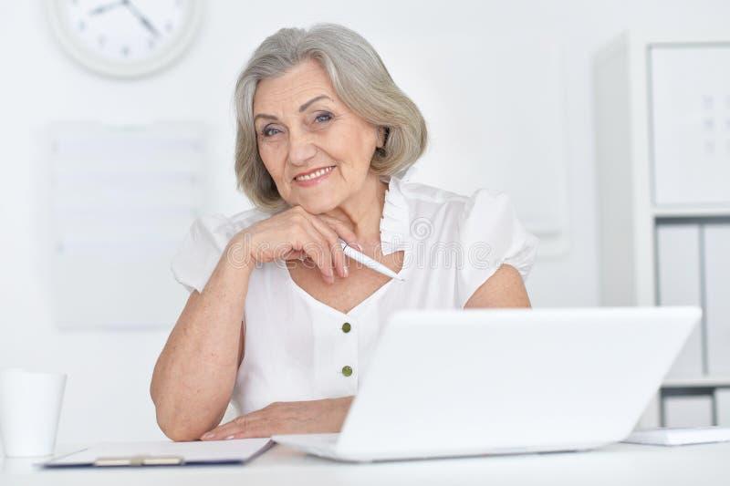 快乐的资深妇女画象有膝上型计算机的在家 库存图片
