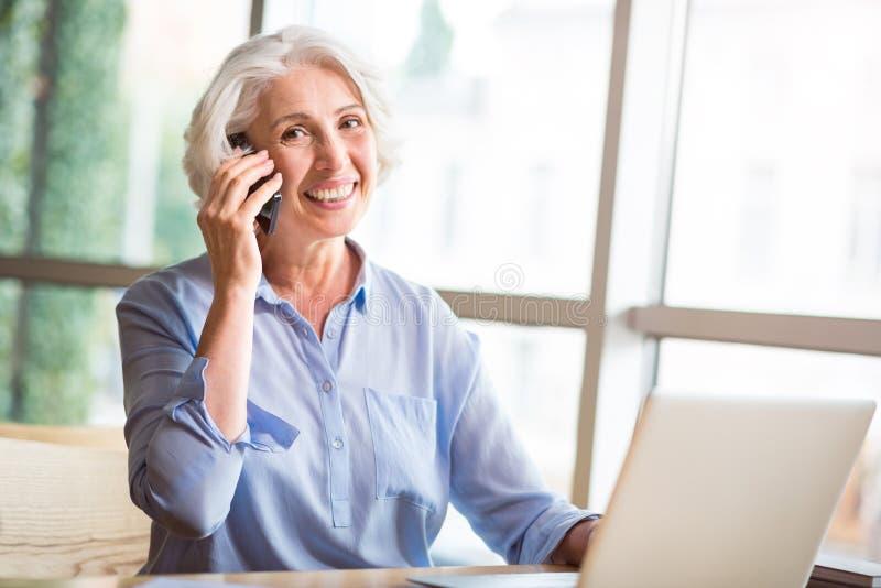 快乐的资深妇女谈话在手机 免版税库存照片