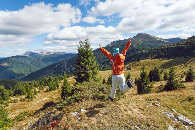 快乐的运动女孩在草坪上跳跃 高山高林高云秋 免版税图库摄影