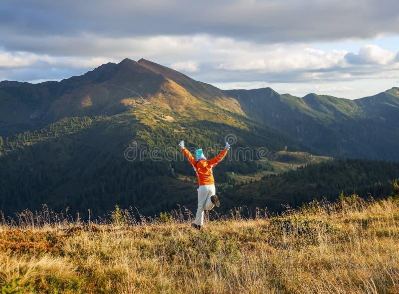 快乐的运动女孩在草坪上跳跃 高山高林高云秋 图库摄影