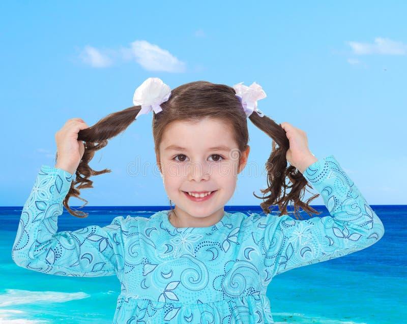 快乐的迷人的女孩用力拖在他的辫子,当时 免版税库存图片