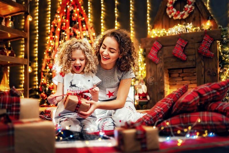 快乐的逗人喜爱的交换礼物的女孩和她的姐姐 免版税库存图片