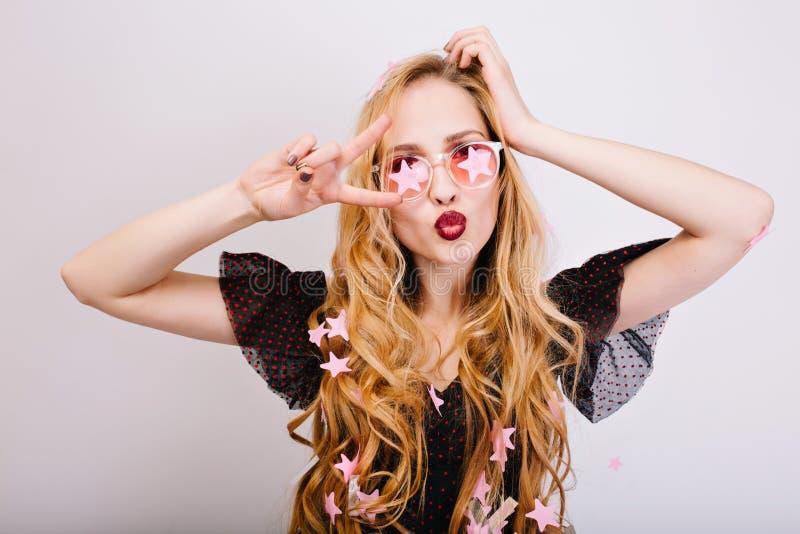 快乐的金发碧眼的女人画象有长的卷发的获得乐趣在党,做滑稽的面孔,显示和平,亲吻对照相机 图库摄影