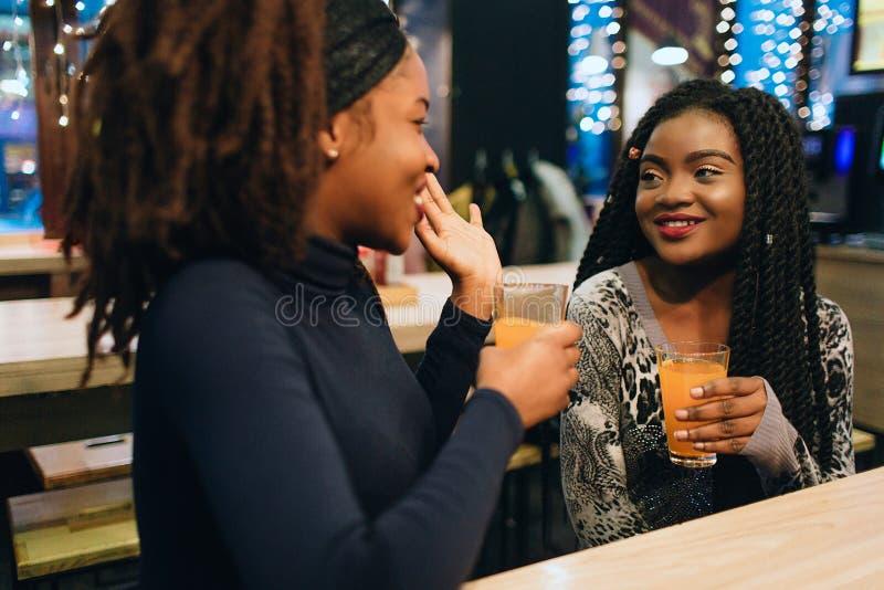 快乐的非洲妇女在咖啡馆和谈话坐 他们互相微笑 模型在手保留玻璃用汁液 免版税图库摄影