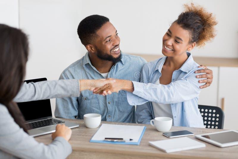 快乐的非洲的配偶和finansial顾问握手在办公室 库存照片