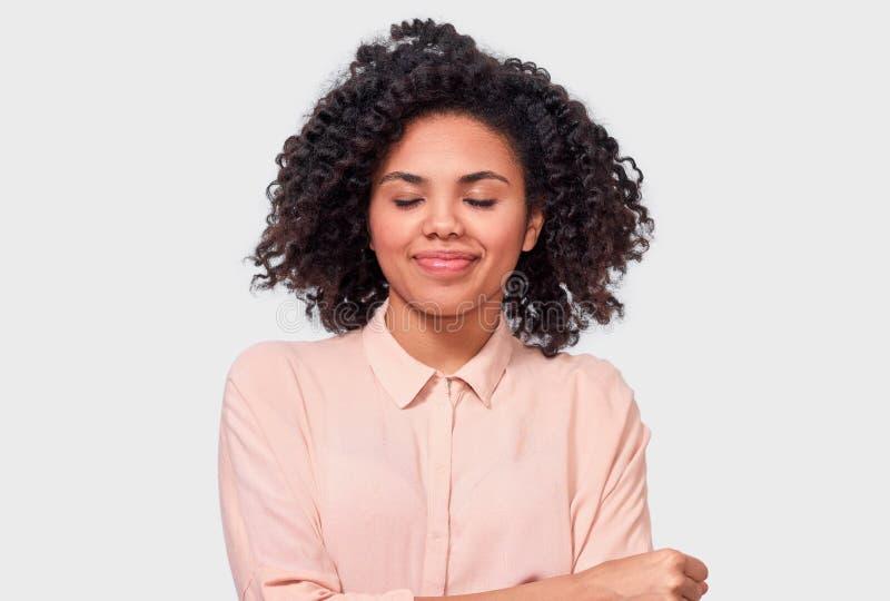 快乐的非裔美国人的年轻女人微笑与闭合的眼睛的,有卷曲非洲的头发的佩带的米黄衬衣,享受美好时光 库存图片