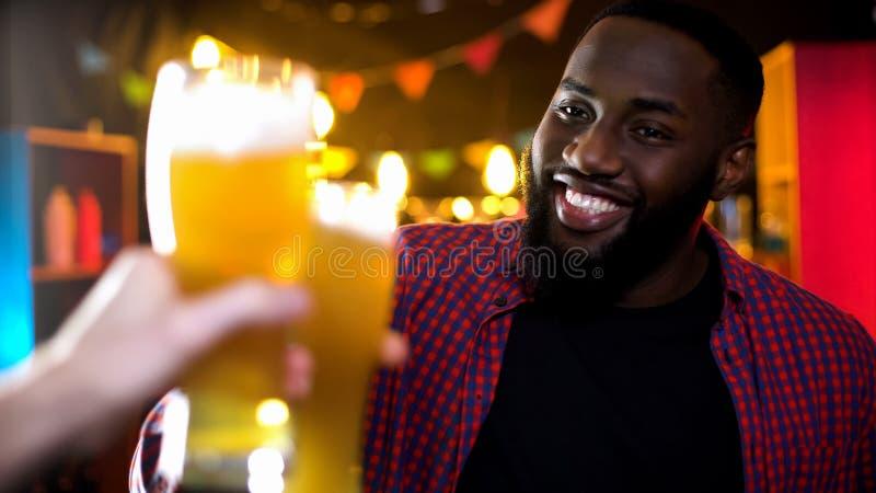 快乐的非裔美国人的男性使叮当响的啤酒杯,享受在酒吧的结果时间 库存图片