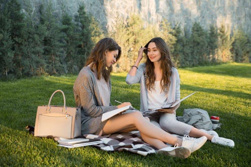 快乐的年轻人坐户外在公园文字笔记的两名妇女 库存照片