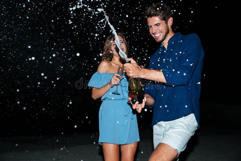 快乐的年轻夫妇饮用的香槟和有乐趣在晚上 图库摄影
