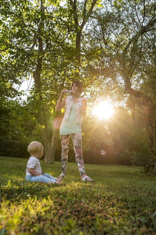 快乐的年轻往她的男婴的母亲吹的肥皂泡 免版税库存照片