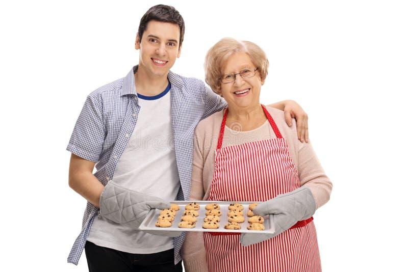 快乐的年轻拿着曲奇饼的盘子人和年长夫人 免版税图库摄影