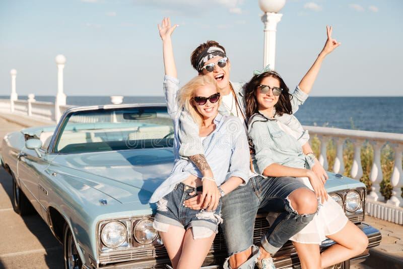 快乐的年轻站立用被举的手的人和两名妇女 库存照片