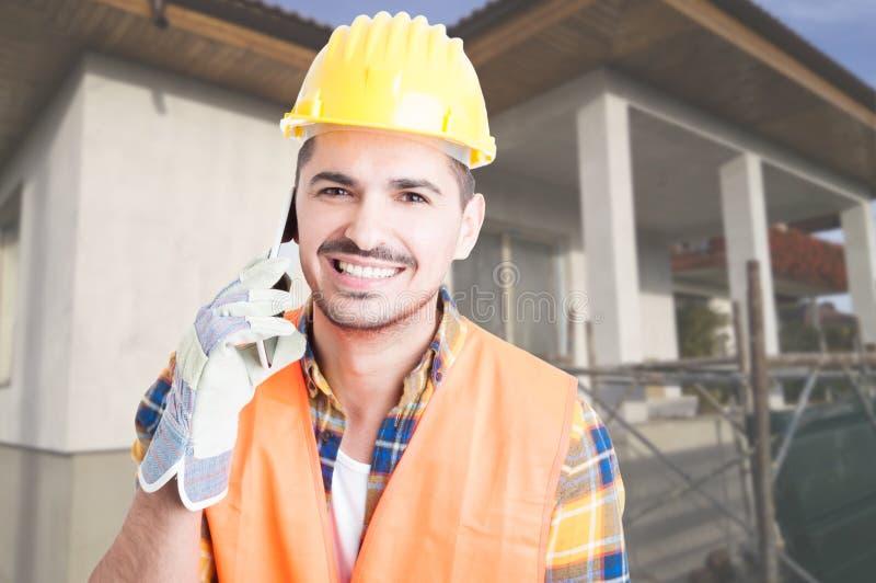 快乐的建筑师画象谈话在智能手机 库存照片