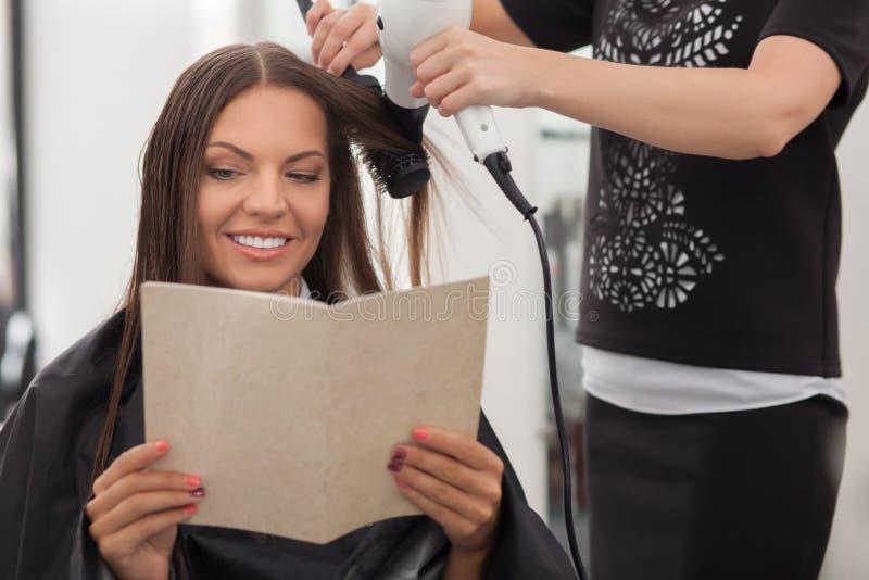 快乐的年轻美发师做一种发型 免版税库存照片