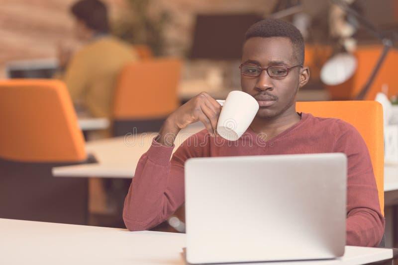 快乐的年轻非洲商人键入的看在膝上型计算机 免版税库存照片