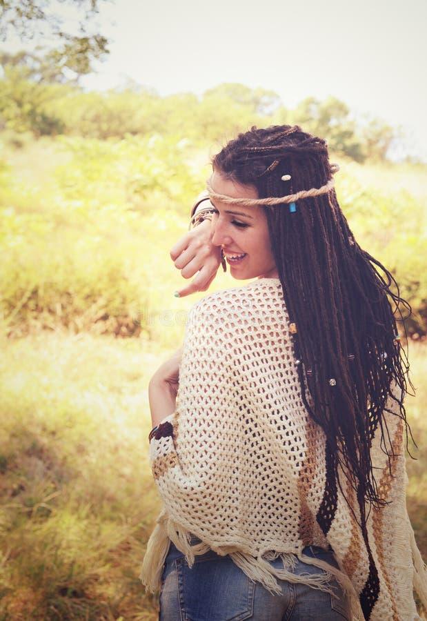 快乐的boho样式女孩画象,穿戴在被编织的雨披和头饰带获得一个乐趣反对晴朗的秋天公园, 免版税图库摄影