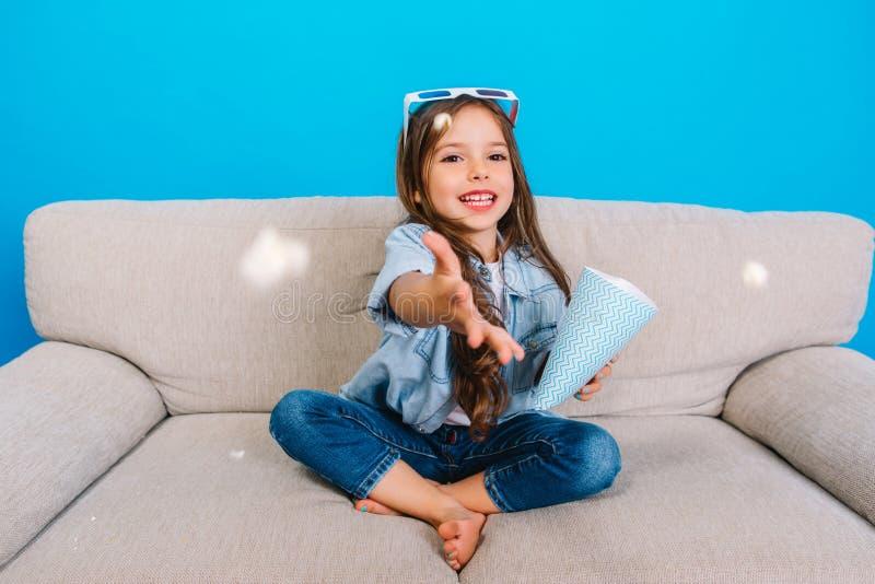 快乐的enterinment用逗人喜爱的俏丽的对照相机的女孩投掷的玉米花从在蓝色背景的长沙发 免版税图库摄影