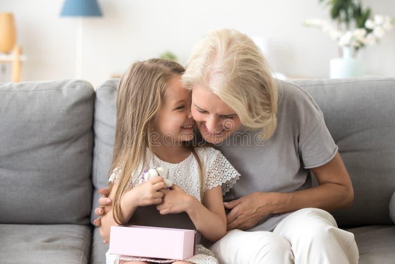 快乐祖母和孙坐的一起笑在长沙发 库存图片