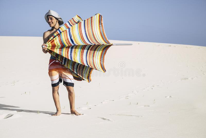 快乐英俊的旅游少年男孩的白种人和获得享用伞太阳的乐趣在美好和白色海滩在夏天 免版税库存照片