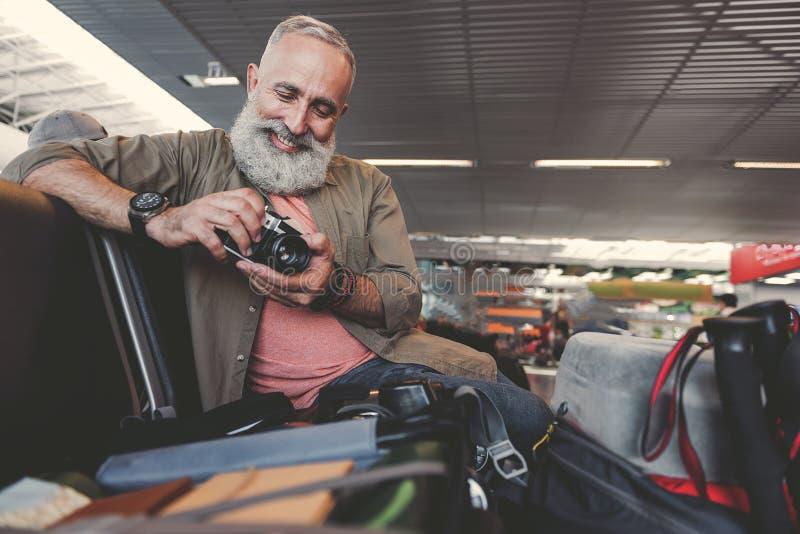 快乐退休保留照相机的人在胳膊 免版税库存图片