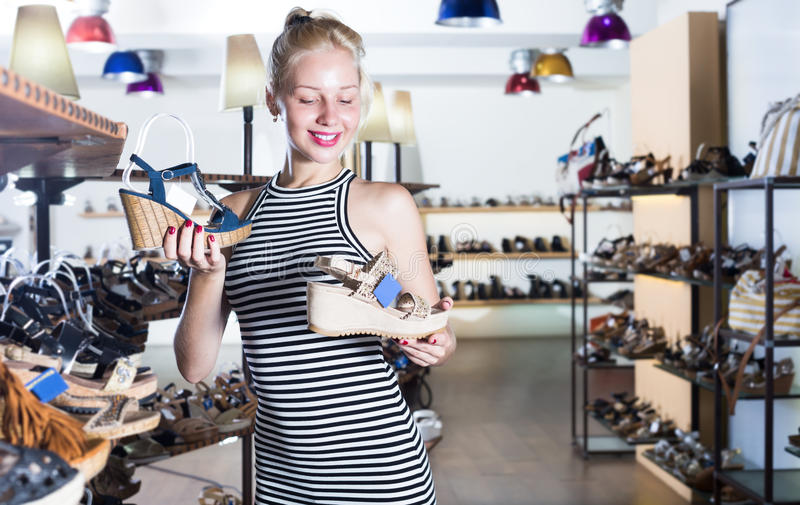 快乐年轻女性看从两个对凉鞋 免版税库存图片