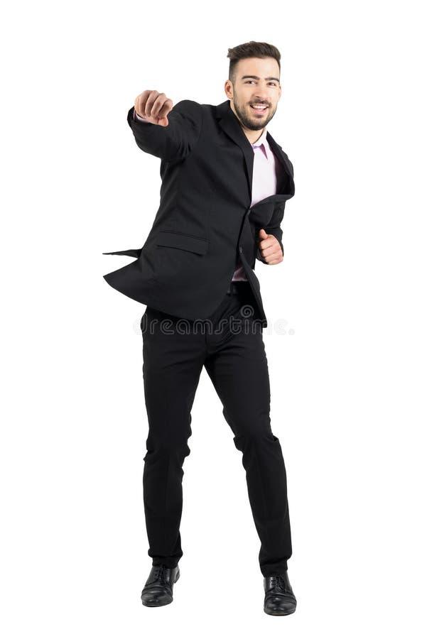 快乐年轻有胡子商人跳跃激发与握紧拳头 免版税库存照片
