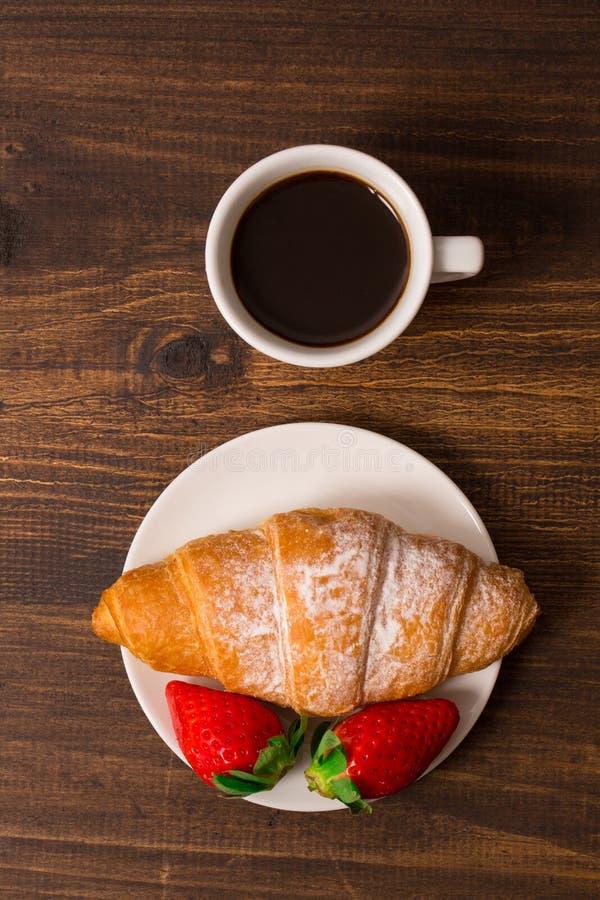 轻快早餐用新月形面包、咖啡和新鲜的草莓 免版税库存照片